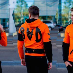 Приобрести в подарок мужскую кофту на молнии с капюшоном оранжевого цвета оптом Украина