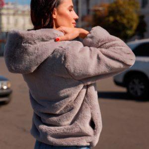 Купить оптом женскую шубку с боковыми карманамим и глубоким капюшоном серого цвета в подарок